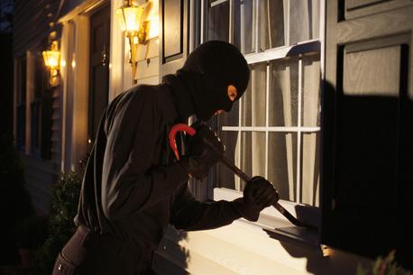 Burglar trying to pry open window on house